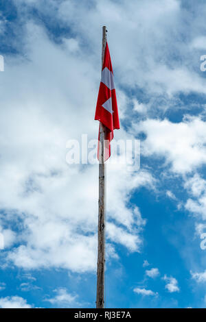Swiss flag hanging limp in still winter air on old wooden flagpole again blue sky with white clouds. - Stock Photo