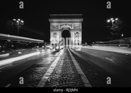 Traffic on Avenue des Champs-Élysées and the Arc de Triomphe at night in Paris, France. - Stock Photo