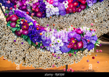 beautiful decoration floral composition or bouquet of seasonal chrysanthemum and eustoma flowers violet and purple colors with dogrose on bamboo sticks in arc shape - Stock Photo