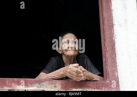 Boca de Valeria, Brazil - December 03, 2015: old mature mulatto woman with kind smiling face holding hands together standing in wooden window brown and white color looking outdoor - Stock Photo