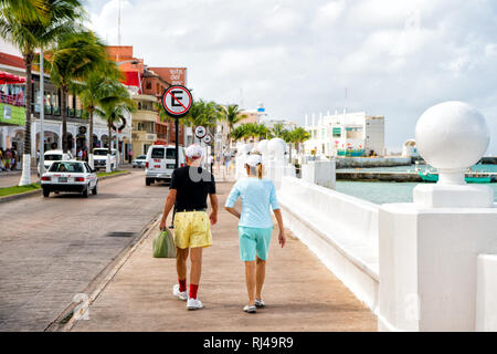 Cozumel, Mexico - December 24, 2015: mature couple of well dressed woman and man walking on street promenade near bay with water and palm trees and cars outdoor in summer - Stock Photo