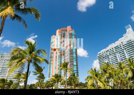Architectural luxury flat building Miami Style South Beach Florida Modern art deco condominium construction aqua and apricot color with palm trees against blue tropical sky background - Stock Photo