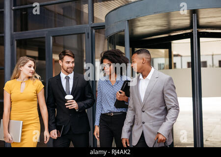 Group of corporate professionals walking out of office together and talking. Business men and women walking through office hallway. - Stock Photo