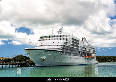 St. Johns, Antigua - March 5, 2016 : Seven Seas Navigator large luxury cruise liner with allservices and full entertainment at the port of st. Jons, Antigua at sunny day - Stock Photo