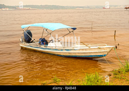 sailing motor boat on dirty water brown color with green grass - Stock Photo
