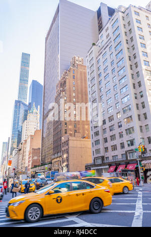 New York - October 17 2016: Yellow cabs, pedestrians and skyscrapers along the streets of Manhattan in New York City.