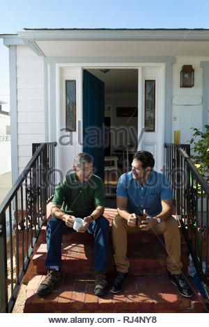 Latinx son and senior father drinking coffee and talking on front stoop - Stock Photo