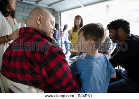 Latinx father and son playing dominos with family in garage - Stock Photo