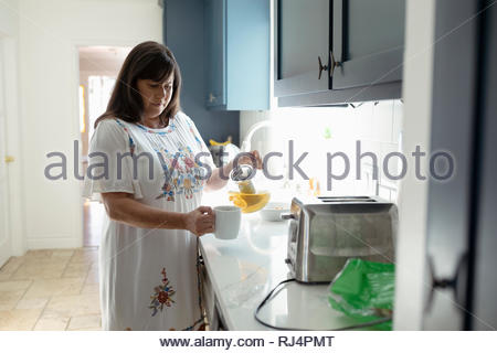 Latinx woman pouring tea in kitchen - Stock Photo