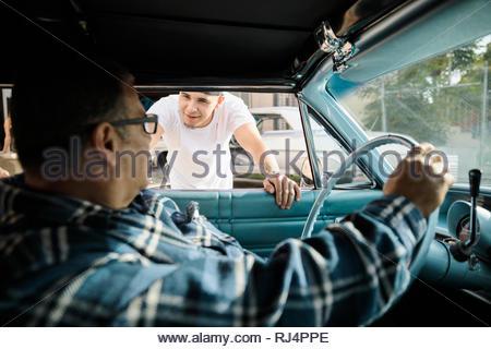Latinx men talking at vintage car - Stock Photo