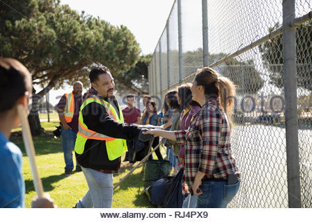 Volunteers shaking hands, cleaning park - Stock Photo