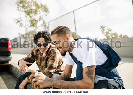 Latinx young men friends using smart phone on urban curb - Stock Photo