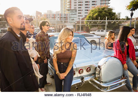 Latinx friends hanging out at vintage car in urban parking lot - Stock Photo