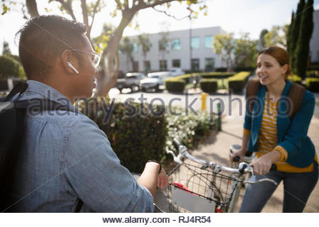 businessman and businesswoman with bicycle talking in parking lot - Stock Photo