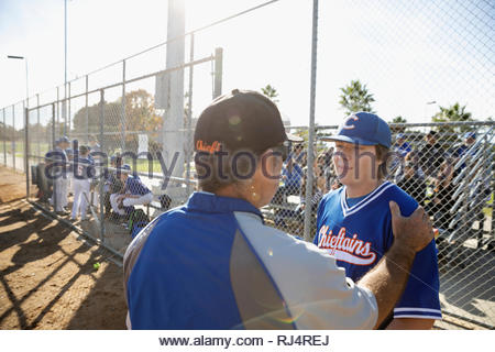 Coach talking with baseball player on sunny field - Stock Photo