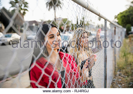 Thoughtful Latinx young women looking beyond fence - Stock Photo