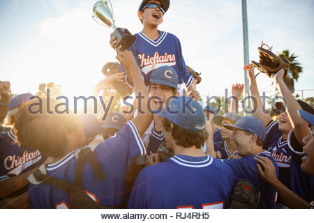 Excited baseball team with trophy celebrating - Stock Photo