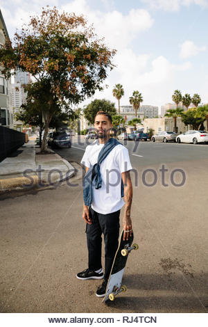 Portrait confident, cool Latinx young man with skateboard on urban street - Stock Photo
