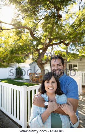 Portrait happy Latinx couple hugging in front of house - Stock Photo