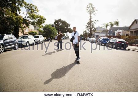 Latinx young men skateboarding on sunny neighborhood street - Stock Photo