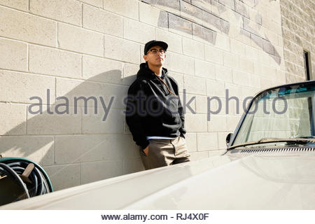 Confident Latinx young man leaning against sunny wall - Stock Photo