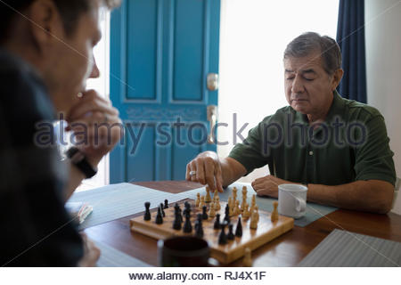Latinx father and son playing chess - Stock Photo