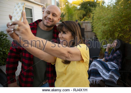 Latinx mother and adult son taking selfie with camera phone - Stock Photo