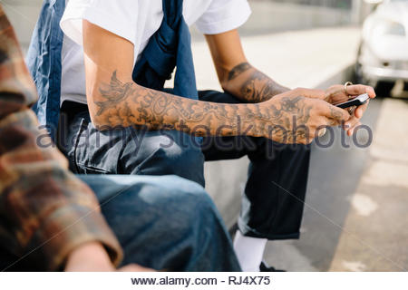 Latinx young man with tattoos on arms texting with smart phone - Stock Photo
