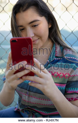 Latinx young woman with smart phone - Stock Photo