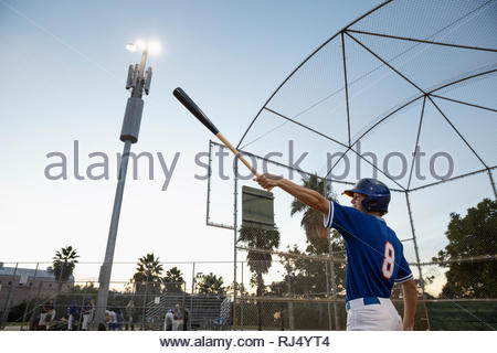 Baseball player swinging bat on field at night - Stock Photo