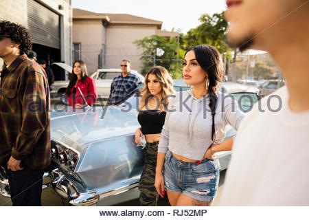 Tough Latinx young women hanging out with friends next to vintage car in parking lot - Stock Photo