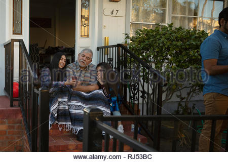 Latinx multi-generation family with smart phone on front stoop - Stock Photo