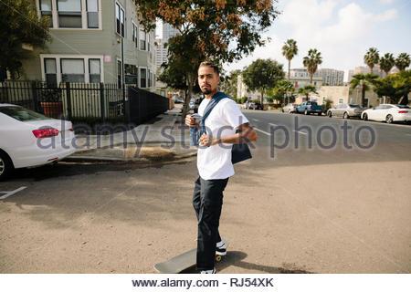 Portrait confident, cool Latinx young man skateboarding on neighborhood street - Stock Photo