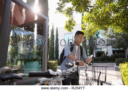Young man with bicycle using smart phone on sidewalk - Stock Photo