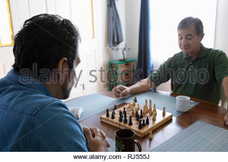 Latinx father and son playing chess at kitchen table - Stock Photo