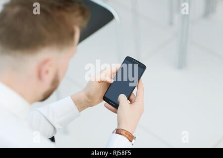 close up.businessman looking at the screen of his smartphone - Stock Photo