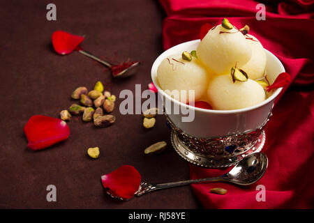 Bowl full with Rasgulla and pistachios, a food table top, Pune, India - Stock Photo