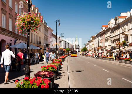 Red geranium flowers planted along street, people walking on sidewalk at Nowy Swiat in Warsaw, Poland, summertime, - Stock Photo