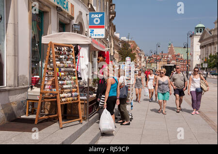 Warsaw souvenirs in stillage in shop front doors, tourist buying souvenirs from Polish capital, pedestrians walking around, Poland, Europe, - Stock Photo
