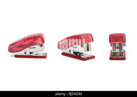 Three pink staplers isolated on white background. - Stock Photo