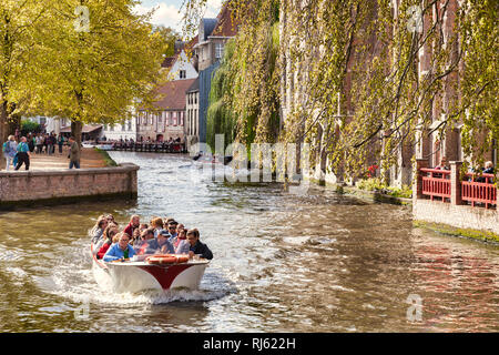 25 September 2018: Bruges, Belgium - Sightseeing boat on the Bruges canal on a sunny autumn day, trees turning to autumn colours. - Stock Photo