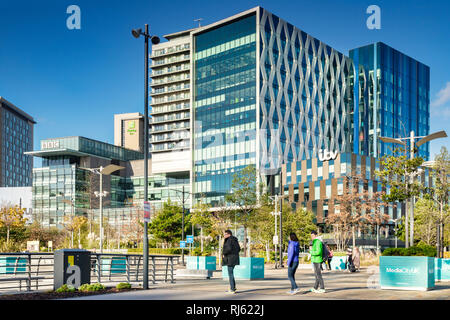 2 November 2018: Salford Quays, Manchester, UK - ITV and BBC buildings on a sunny autumn day, clear blue sky, colourfully dressed young people in... - Stock Photo