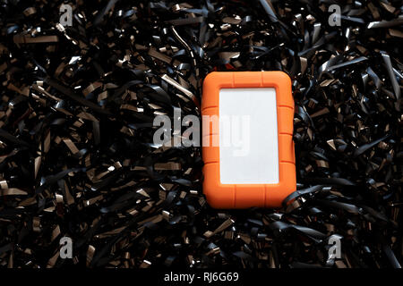 LaCie Portable storage device, no logo, on a bed of magnetic tape. - Stock Photo
