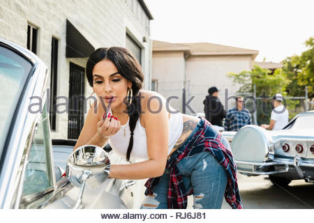 Latinx young woman applying lip gloss in side view mirror of vintage car - Stock Photo