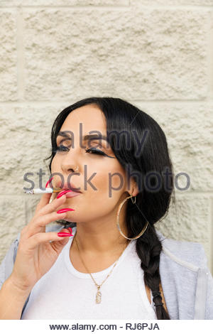 Latinx young woman smoking cigarette - Stock Photo
