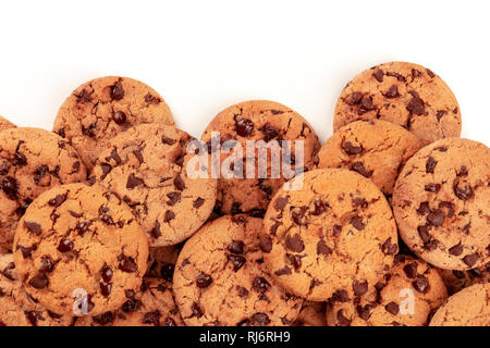 Many freshly baked chocolate chip cookies, shot from the top on a white background, an abstract sweet biscuits texture with copyspace - Stock Photo