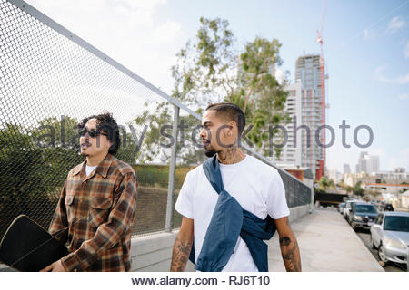 Latinx young men with skateboard walking on urban sidewalk - Stock Photo