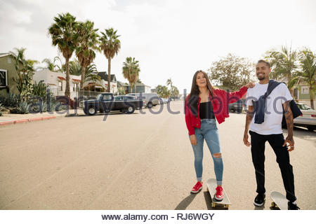Portrait happy Latinx couple skateboarding on sunny neighborhood street - Stock Photo