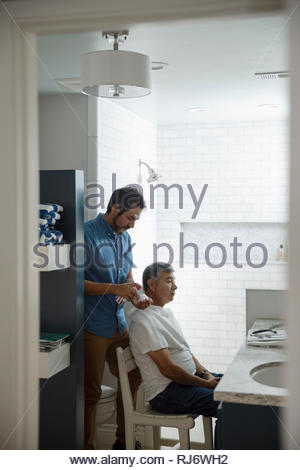 Latinx son preparing to shave senior father s face in bathroom - Stock Photo