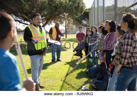 Man in reflective vest leading meeting for volunteers cleaning sunny park - Stock Photo